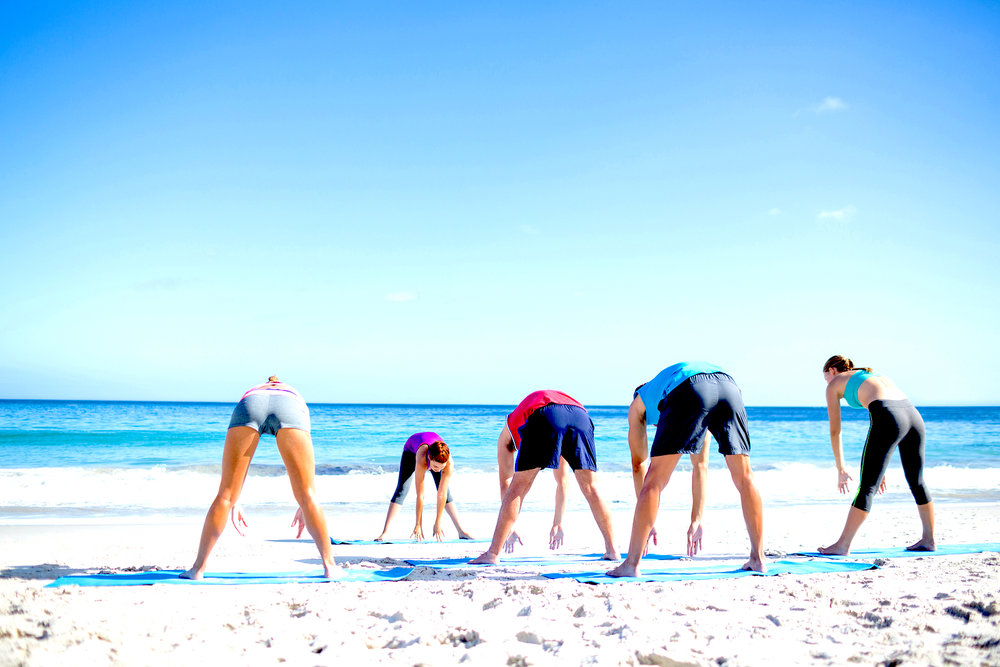 Guests stretching on the beach at Vita Vie Retreat.