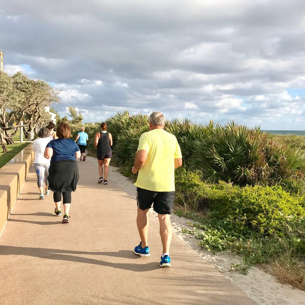 Guests warm up on the ocean view sidewalk during their retreat.