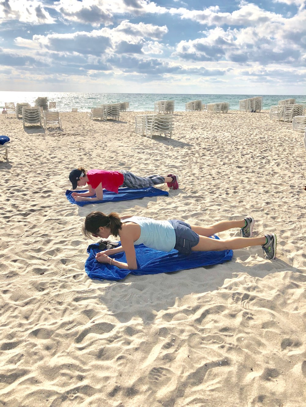 Ladies workout during Sunday Core + Stretch class on the beach in Delray Beach, FL.