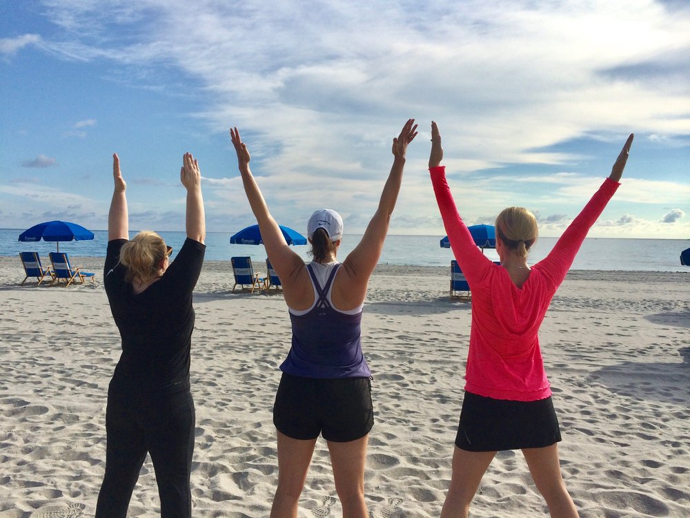 Clients celebrate their retreat with arms in the air.