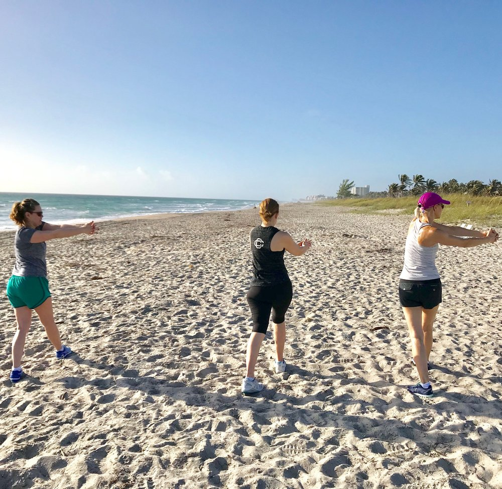 Guests begin the morning at the beach with dynamic stretch.