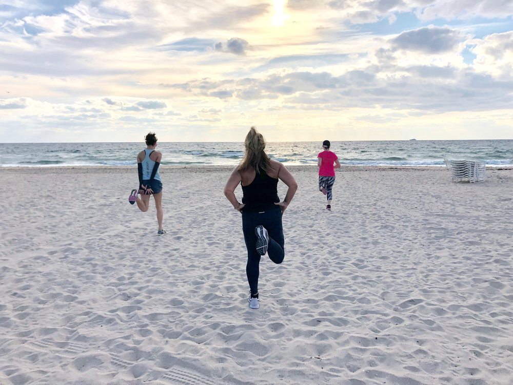 Ladies working out during their fitness retreat on the beach.