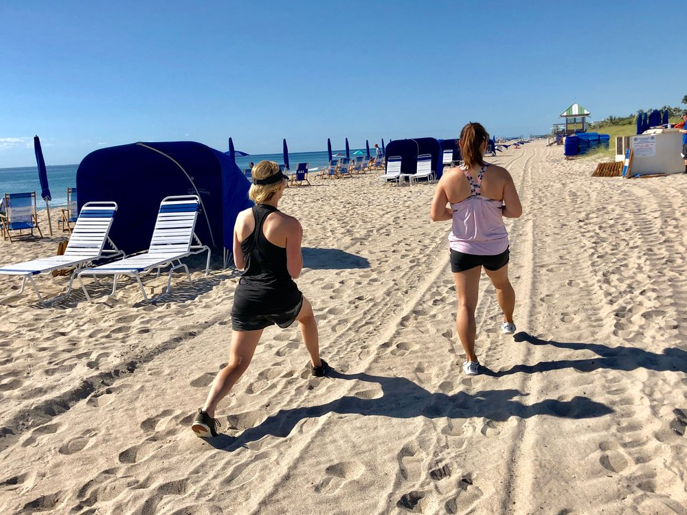 Lunges on beach during fitness retreat.