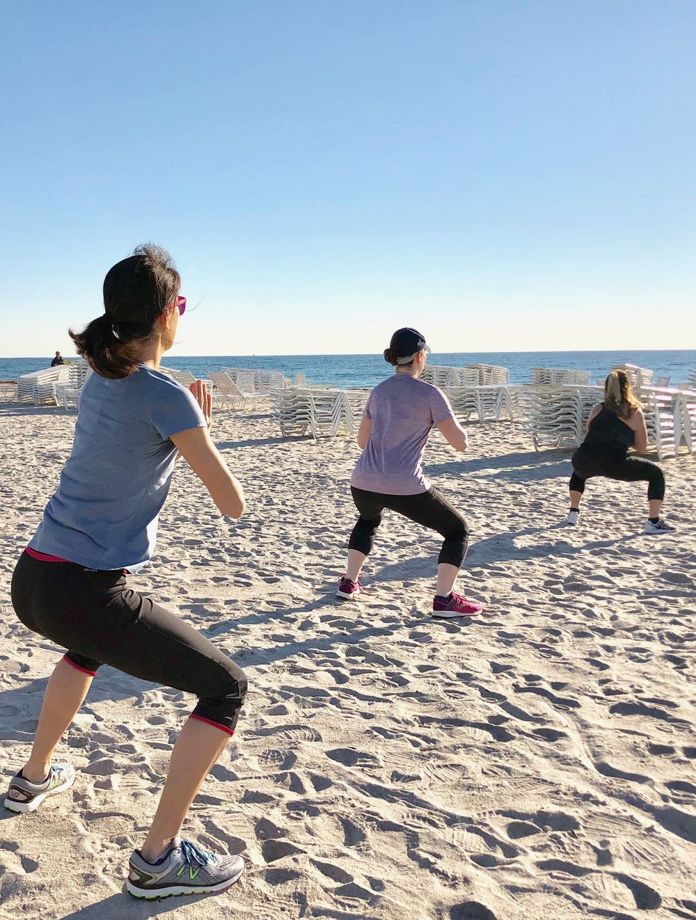 Fitness class squats on the beach.