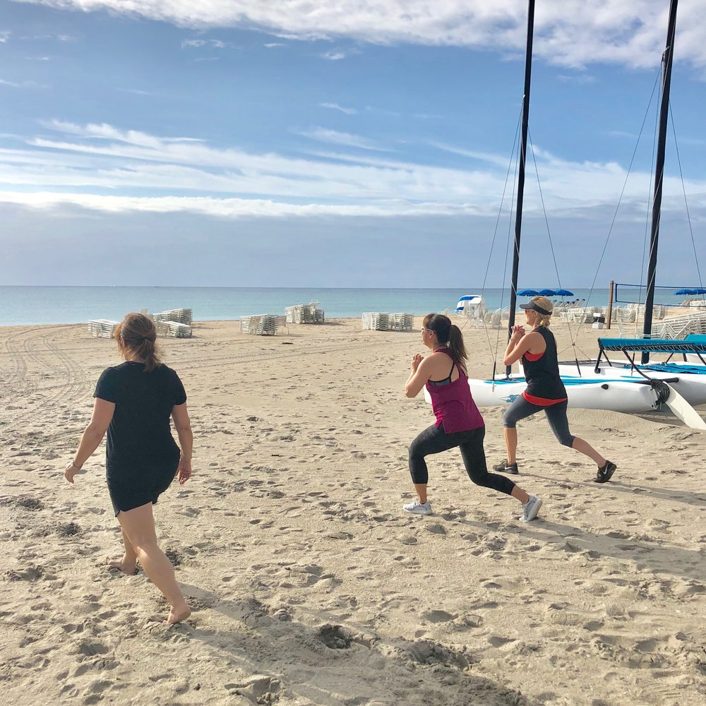 Clients lunging during beach fitness class in Delray Beach, FL