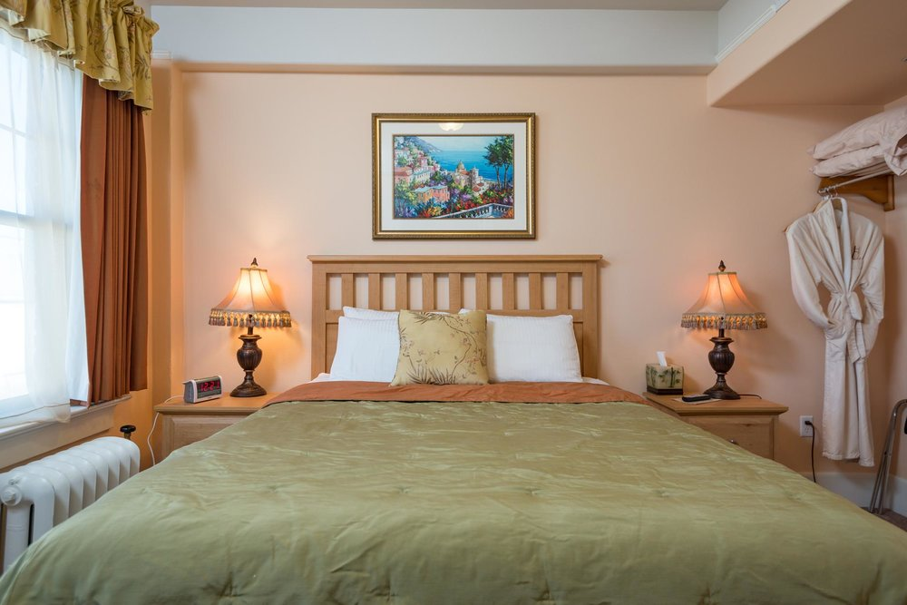 Deluxe Suite - At least 220 square feet. Bedroom with queen bed and separate sitting room with double sofa bed. Bathroom with walk in shower. Sleeps 4 guests and up to 2 children. Complimentary wifi and continental breakfast.