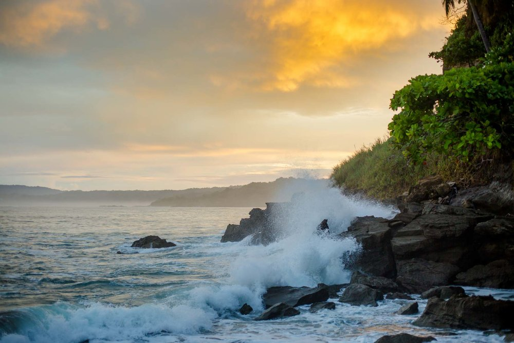 Beach sunset with waves crashing agains rocks