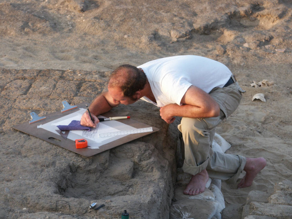 Fig. 1. Architectural illustrator Damon Cassiano planning a Middle Kingdom chapel in the Abydos North Cemetery. Photo: Robert Fletcher / North Abydos Expedition © 2003