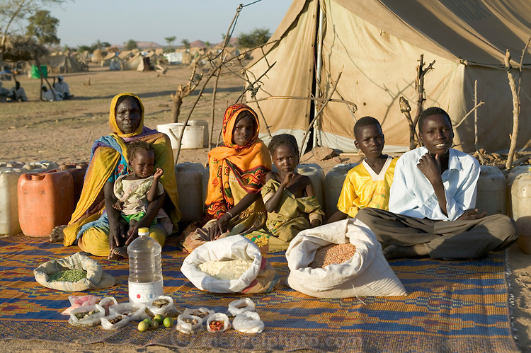 CHA104.0001.xxf1rw (MODEL RELEASED IMAGE) The Aboubakar family of Darfur province, Sudan, in front of their tent in the Breidjing Refugee Camp, in eastern Chad, with a weekÕs worth of food. DÕjimia Ishakh Souleymane, 40, holds her daughter Hawa, 2; the other children are (left to right) Acha, 12, Mariam, 5, Youssouf, 8, and Abdel Kerim, 16. Cooking method: wood fire. Food preservation: natural drying. Favorite foodÑDÕjimia: soup with fresh sheep meat. /// The Aboubakar family is one of the thirty families featured in the book Hungry Planet: What the World Eats (p. 56). Food expenditure for one week: $1.23 USD. (Please refer to Hungry Planet book p. 57 for the familyÕs detailed food list.)
