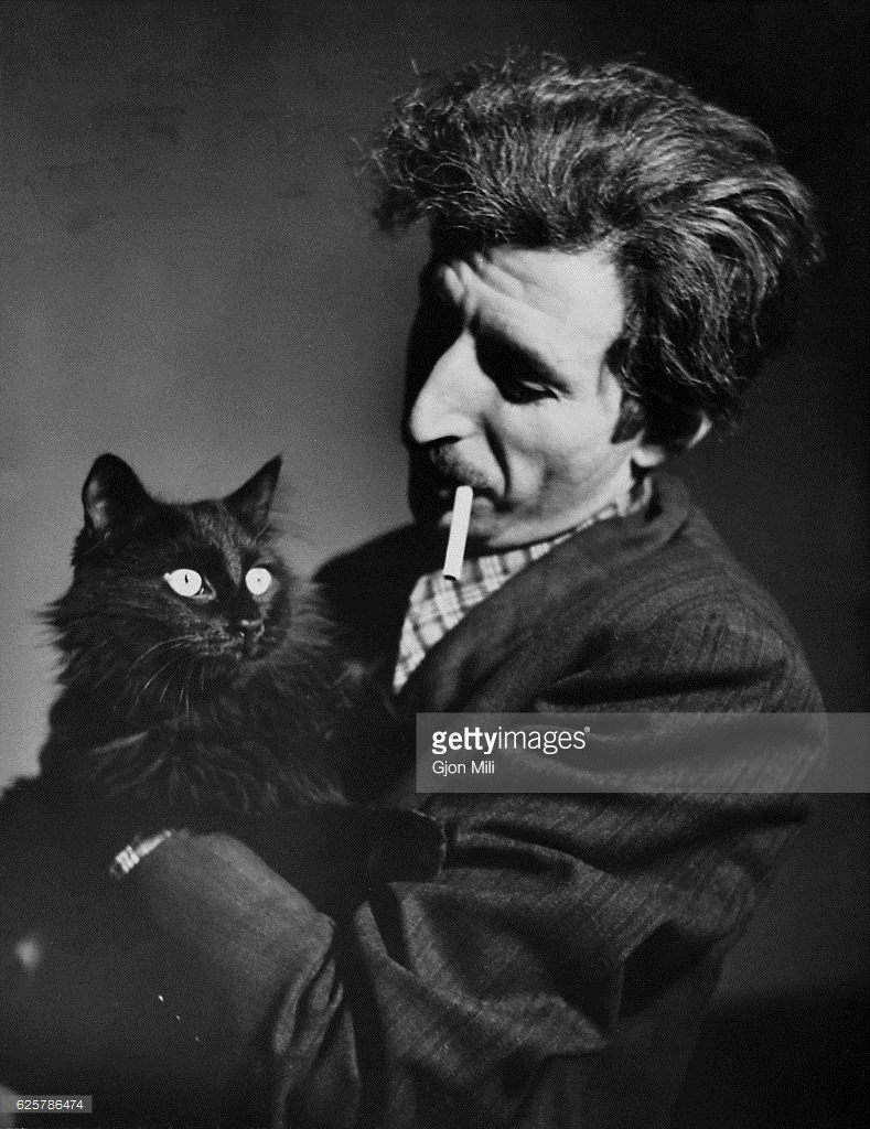 Subject: LIFE photographer Gjon Mili smoking cigarette and holding his beloved cat named Blackie. New York, NY 1946 Photographer- Gjon Mili Time Inc Owned merlin- 112522335