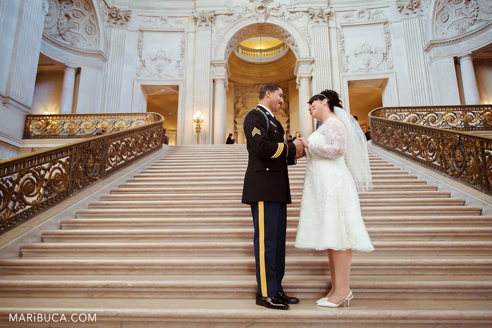 The bride and the groom are looking each other and smile in the staircase before wedding ceremony in the San Francisco City Hall