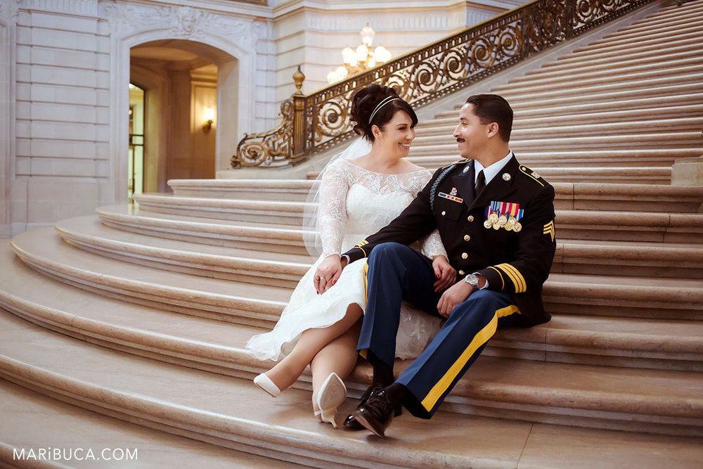 The bride and the groom are sitting in the staircase and laugh each other in the SF City Hall wedding.
