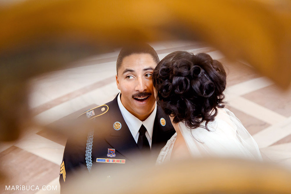 The bride is kissing the groom with the dark blue military suit in the cheek in the SF City hall.