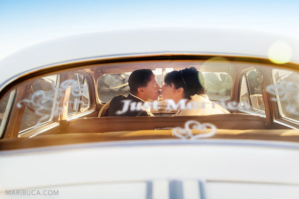 """The bride and groom kiss each other in the Pontiac car and the sticker on the car's window """"just married"""""""