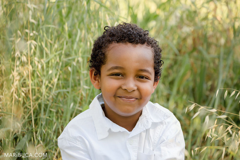 the boy smiling portrait in the green grass