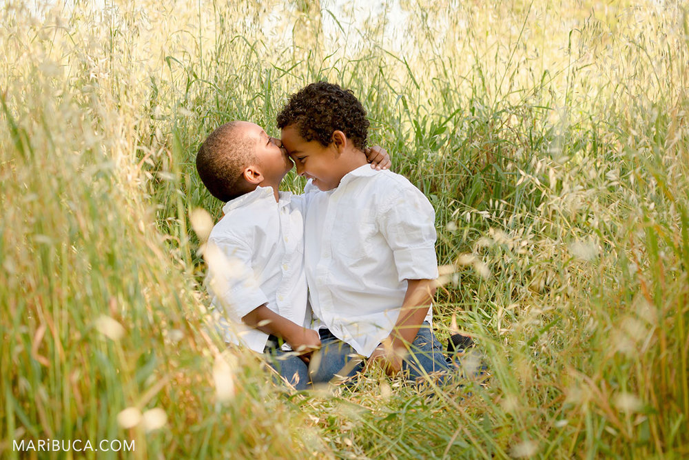 brothers show how their care about each other in the park. One of them kissing his brother in the forehead.