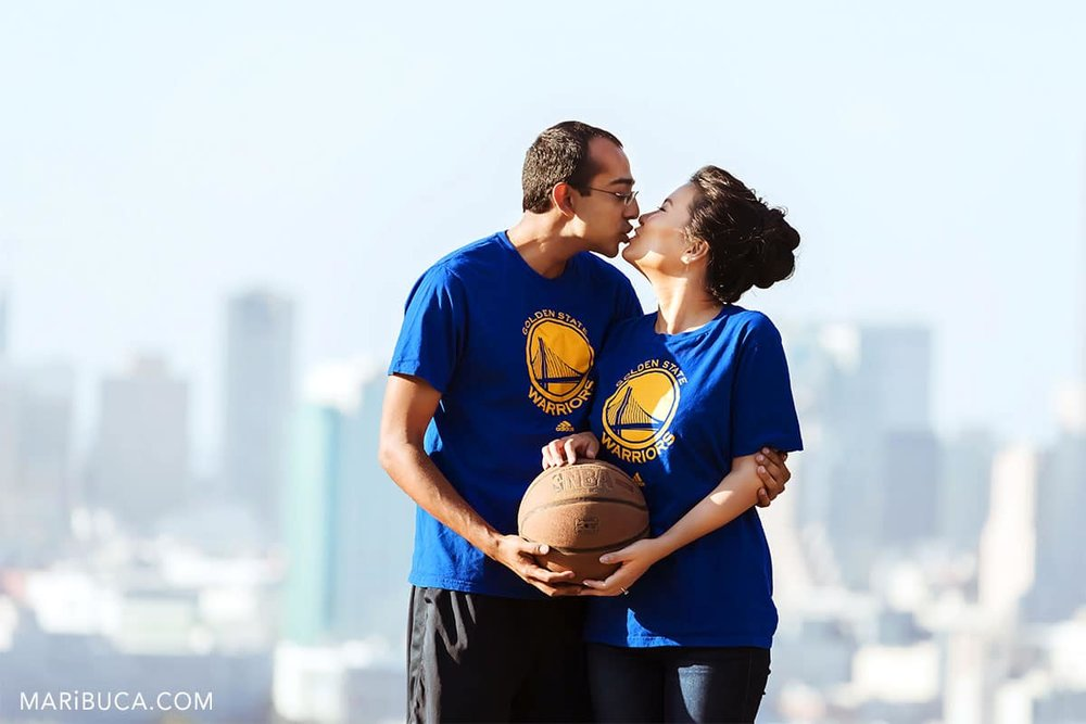 fiancee and fiance kissing and holding basketball.