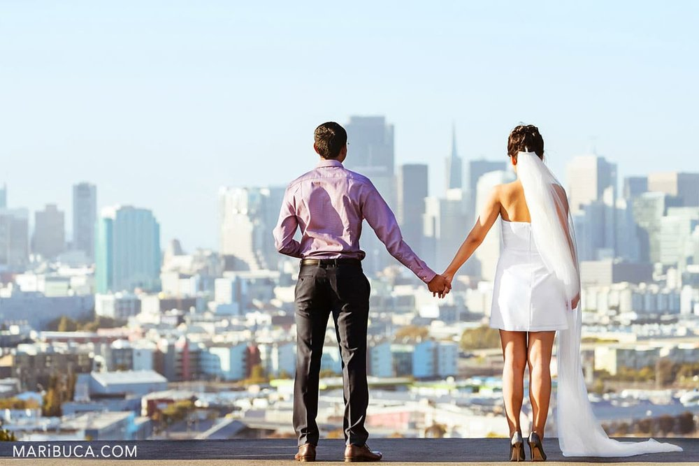 fiancee and fiance holding hand and look in the San Francisco view