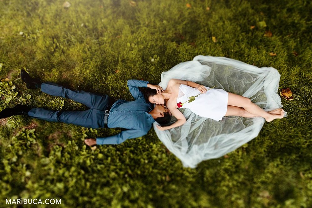 couple lay down in the grapp and kissing. Wedding kiss in the grass.