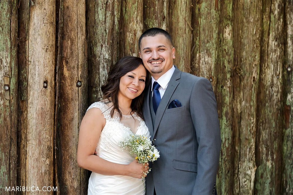 Portraits happy and lovely newlyweds couple and wooden background
