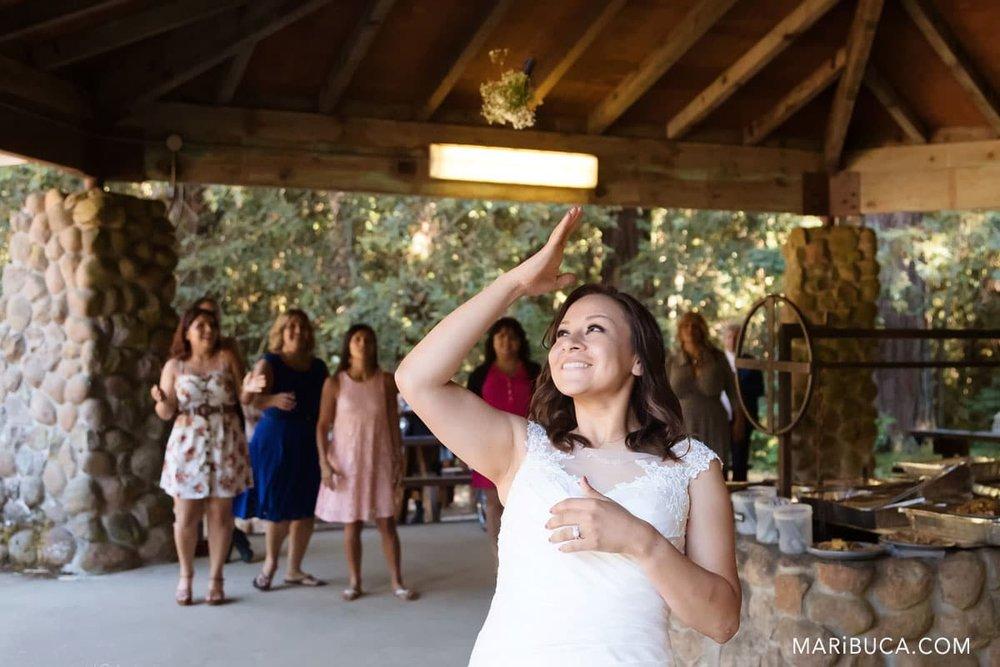 the bride throws bouquet to bridesmaids