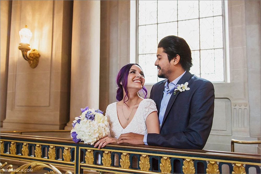 The bride and the groom are looking each other in the SF City Hall