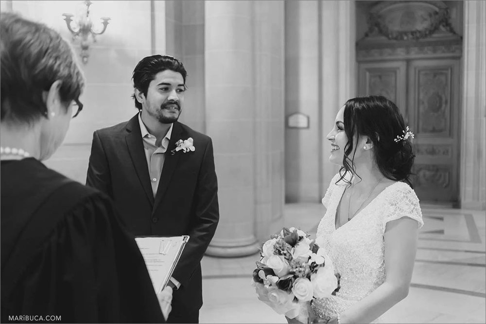 The black and white image. The groom and the bride are looking each other in the wedding ceremony in the SF City Hall