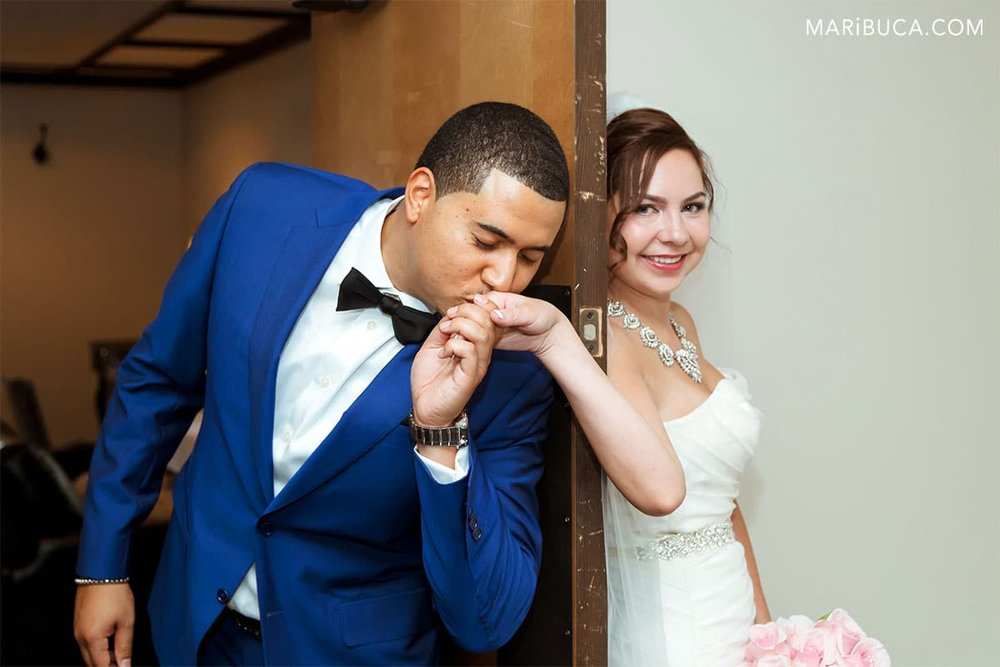 The groom during the first look without look is kissing the bride. The bride is smiling.