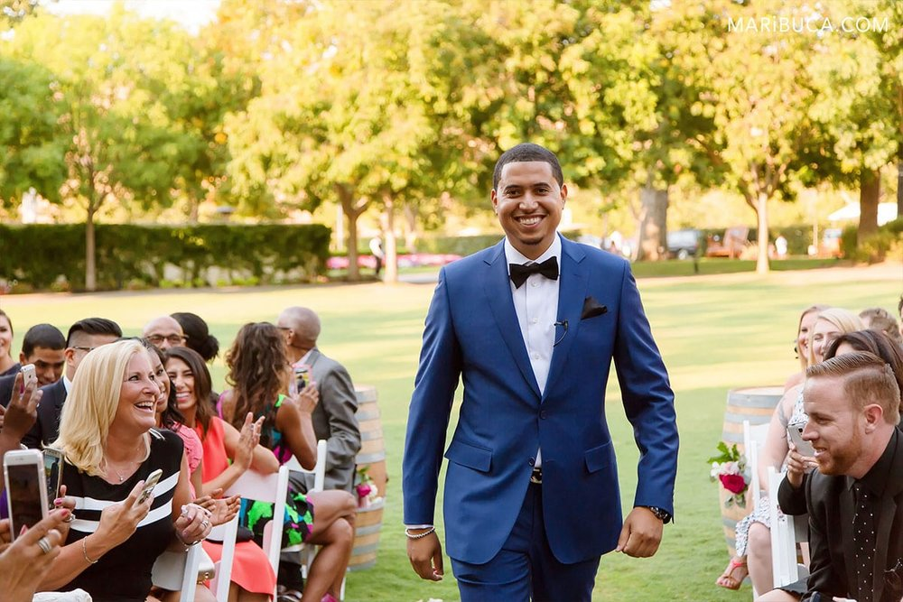 Outdoor ceremony starting and the groom go down the aisle in the Wente Vineyards