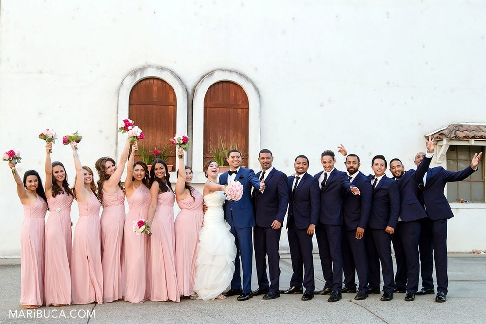 bridesmaids, groomsmen and newlyweds ready to take pictures. Funny faces.