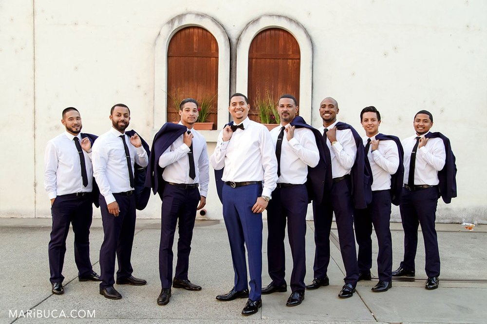 The groom and groomsmen have fun for taking pictures.