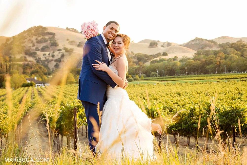 Groom & bride take pictures during sunset time in the vineyard.