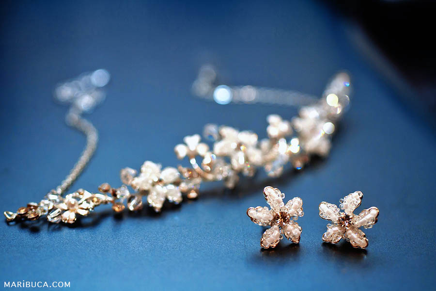 Jewelry for the bride such as necklace and earrings lying on a blue background.
