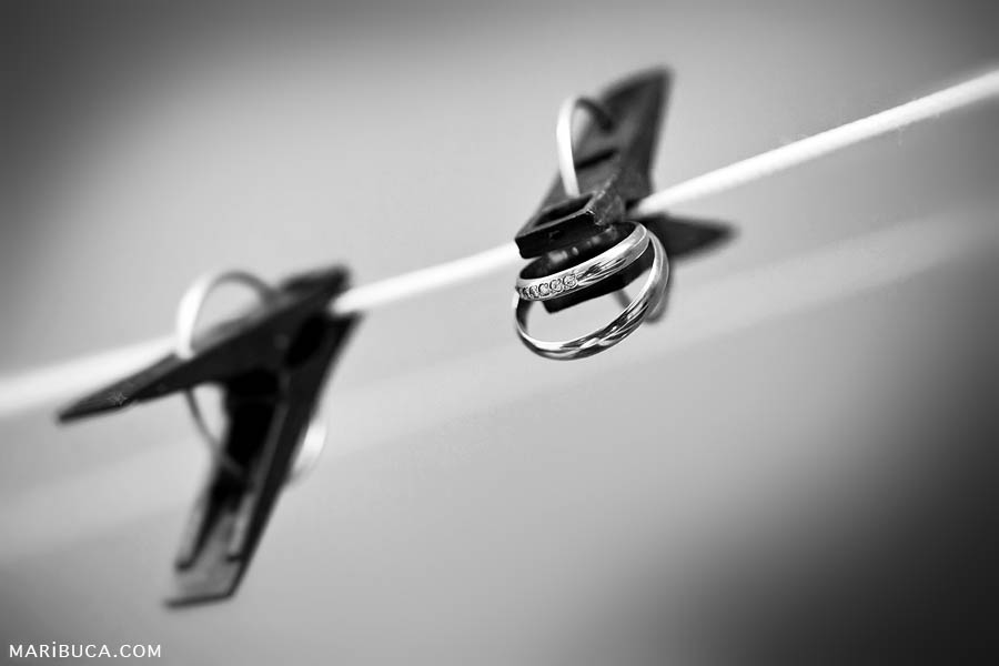 black and white photo of clothespins with wedding rings