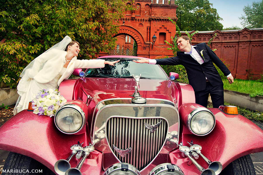 Bride and groom reaching out over the red retro limo