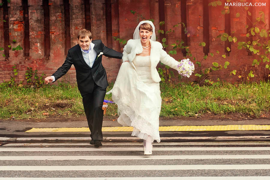 Bride and groom run through a pedestrian crossing and shout from happiness against the background of a red brick wall in San Francisco