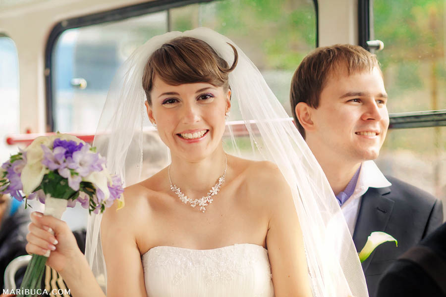 bride and groom smile and ride the tram to their wedding
