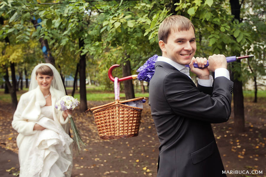 the bride and groom walk through the streets with an umbrella because their limo is broken.
