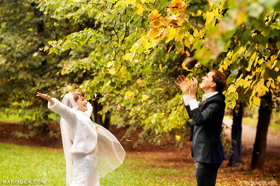 bride and groom throw up foliage in the park in Indian summer in the Golden Gate Park.