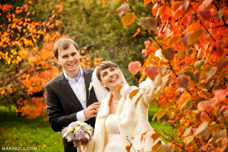 the bride and groom laugh and walk in the park on the wedding day on the background of orange and green trees in the Golden Gate.