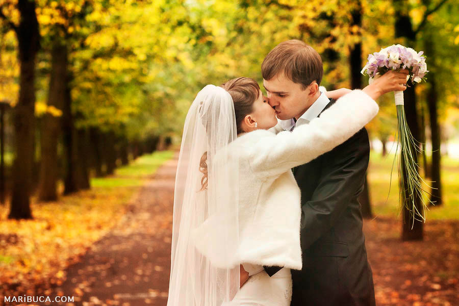 newlyweds kiss each other against the backdrop of a yellow forest in Indian summer
