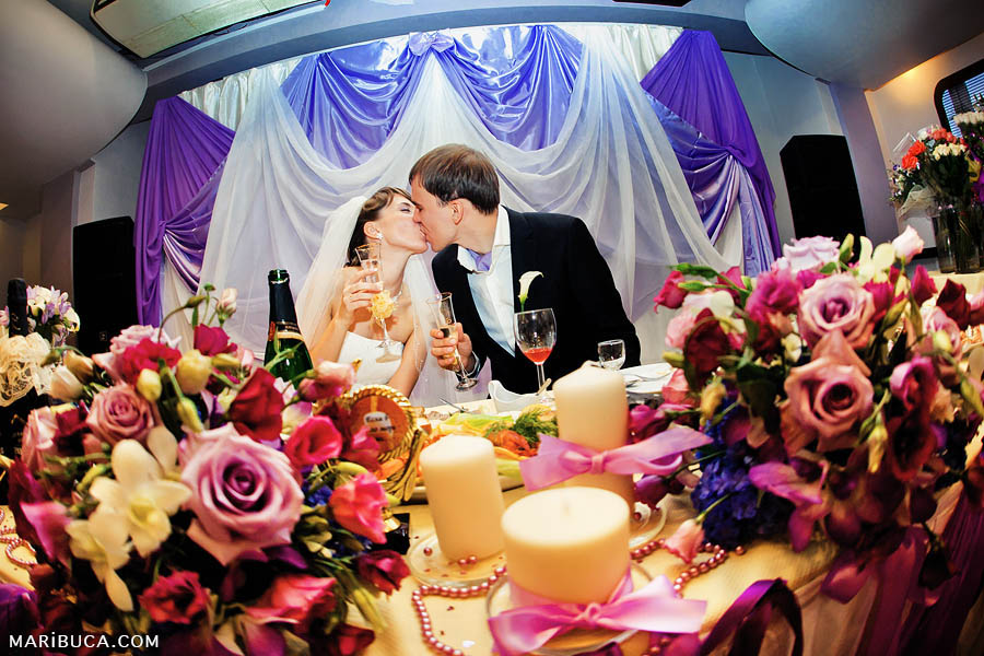 the bride and groom kiss each other against the background of purple fabrics and a luxurious wedding table during their reception.
