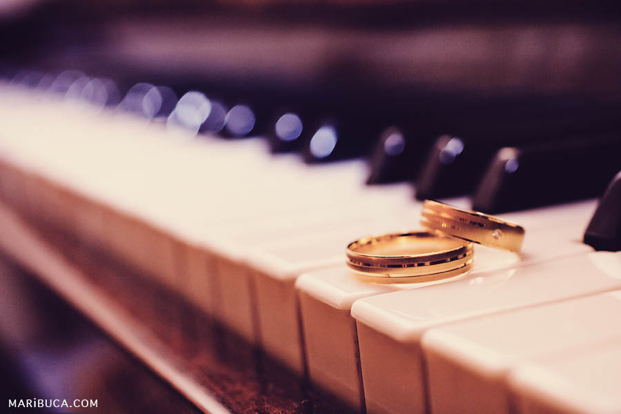Details: golden wedding rings lying on the piano.