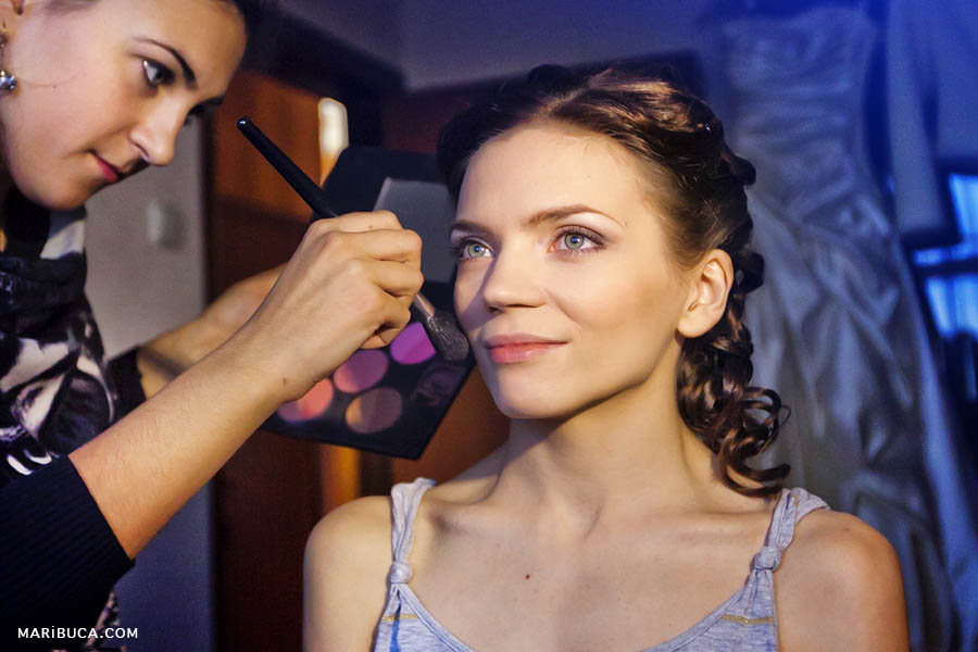 Makeup time for the bride in your wedding day in the navy blue background.