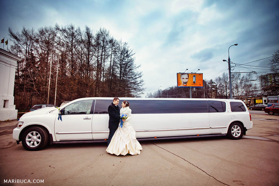 Bride and groom stand on the background of a long white limousine in Hayward
