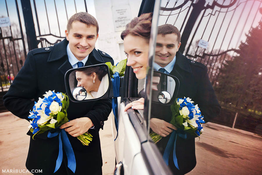 The groom stands against the car, and the bride sits like a limousine and smiles and you can see the reflection in the mirrors of the newlyweds.