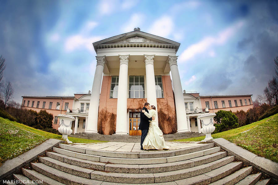 bride and groom on nature in the park kiss each other against the background of the historic building in Hayward