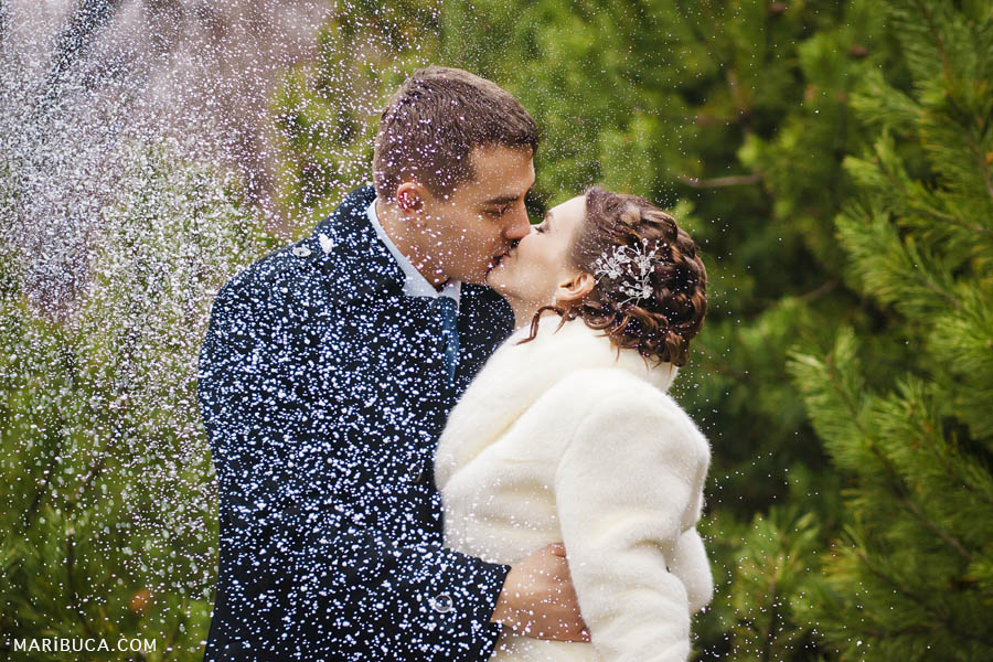 the bride and groom kiss each other and it snows in winter weather on the background of the trees.