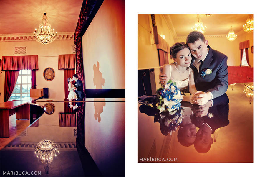 Bride and groom in a historic building kiss each other and a shadow on their wall.