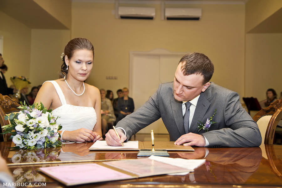Groom signs in the marriage licence in the register office and the bride looks at him.
